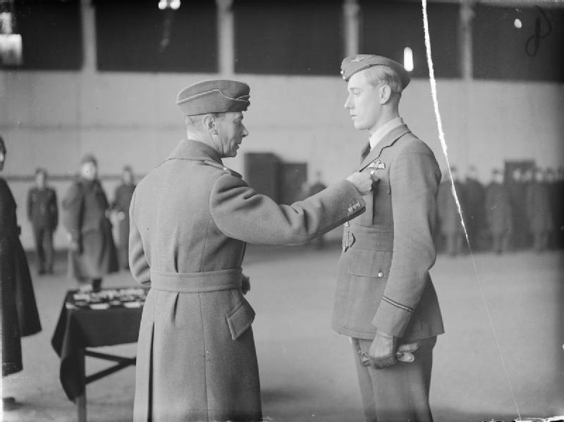 King George VI conferring a Bar to Flying Officer A G Lewis's DFC in an awards ceremony at Duxford, Cambridgeshire. Lewis, a South African, had just returned to service with No. 249 Squadron RAF, after being shot down and badly burnt on 28 September 1940, at which time he had himself shot down 18 enemy aircraft. Photo copyright IWM collection.